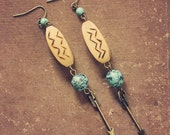 arie.  a pair of wood and teal arrow earrings.
