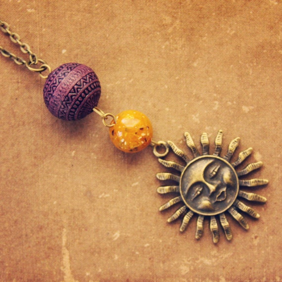 RESERVED earthlight.  a purple and orange beaded sun pendant.