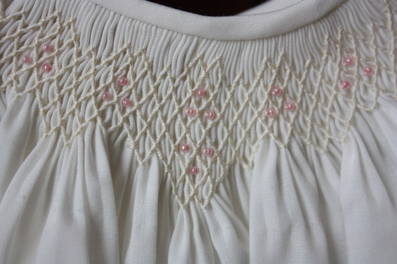 Hand-smocked infant girl daygown, off-white with pink glass beads