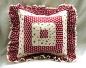 red-white pillow with ruffles