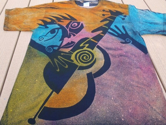 Abstract design of a person playing a guitar in beautiful bright colors, discharge t-shirt, then over dyed.