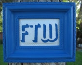 """Blue embroidered """"FTW"""" wall hanging"""