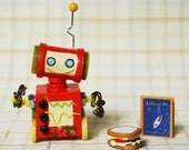 Red Miniature Wooden Robot with a Book and a Light Snack