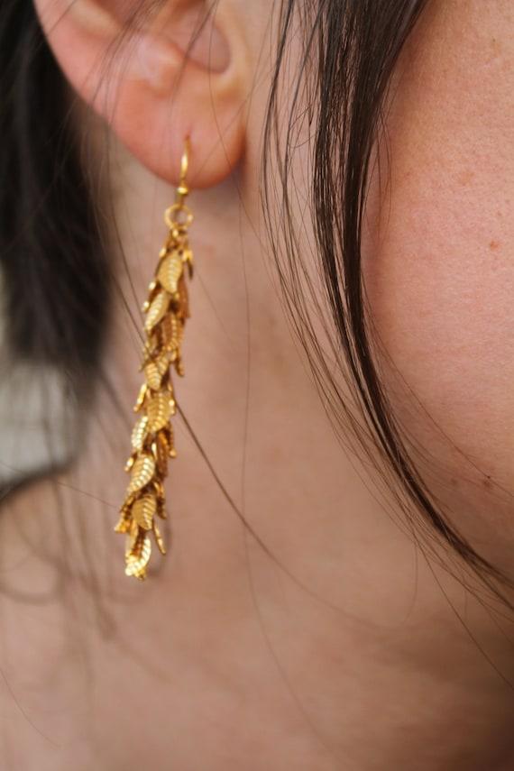Long gold dangling earrings,Delicate, dangling Goddess-earrings with cascading leaves in gold , gold dangle earrings