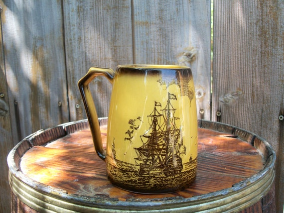 Nautical coffee mug featuring two old time sailing or pirate ships