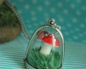 Collier globe champignon rouge à pois blanc avec sa coccinelle sur un lit de pelouse