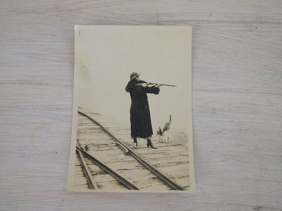 vintage black and white lady in fur on railway with rifle photo from australia