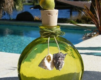 Chartreuse glass bottle adorned with seashells. Fill with perfumes, lotions, salts, or essential oils. Great gift.