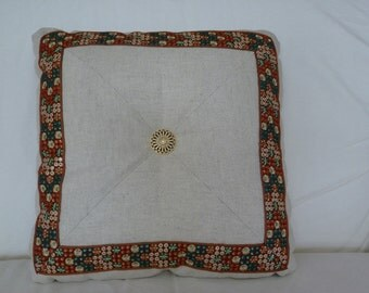 Embroidered trim on natural, tufted pillow