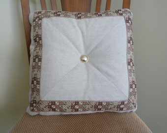 Embroidered trim and tufted pillow
