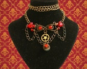 Steampunk choker necklace with flame-coloured jewels, hanging chain detail and vintage cog