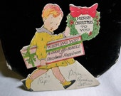 Adorable 1920's die cut christmas card little boy with large gift and wreath in hand