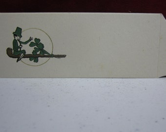 Vintage unused gold gilded 1920's-30's St. Patricks Day Place card with Leprechaun sitting on a pipe with green clovers, shamrocks