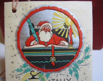 1930's die cut Colorful hand colored silver gilded  parchment paper bridge tally card santa claus sitting and checking his list