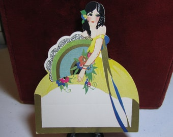 Art Deco unused 1920's-30's die cut  gold gilded place card black haired lady holding large fan flowers tied to wrist