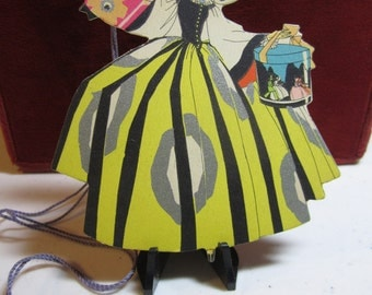 Unused die cut buzza bridge tally card girl in bonnet with elaborate dress holding two hat boxes  one with crinoline ladies