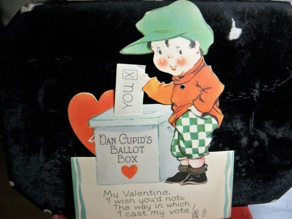 Vintage die cut mechanical 1920's valentine's day card boy wearing plaid knickers placing his ballot in Dan Cupid's Ballot box