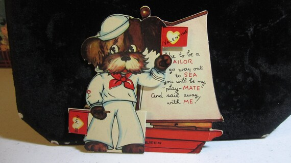 1930's-40's die cut valentine with a dog dressed in a sailors outfit in front of a sail boat