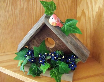 Barnwood Decorative Birdhouse, navy blue flowers with ivy and a pink bird perched on roof