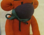 Cashew the bright orange and purple Sock Monkey Doll with a green ribbon