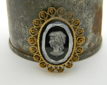 Black glass carved vintage cameo with ornate gold trim