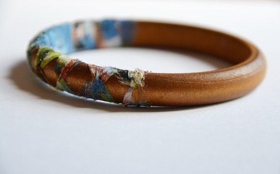 Wood and fabric bangle. Summer tribal fabric hand knotted around wooden bangle.  Blue/green color. Light weight Small size.
