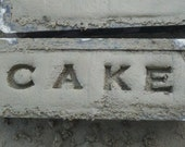 Hand cast, Hand stamped cement block with the word Cake