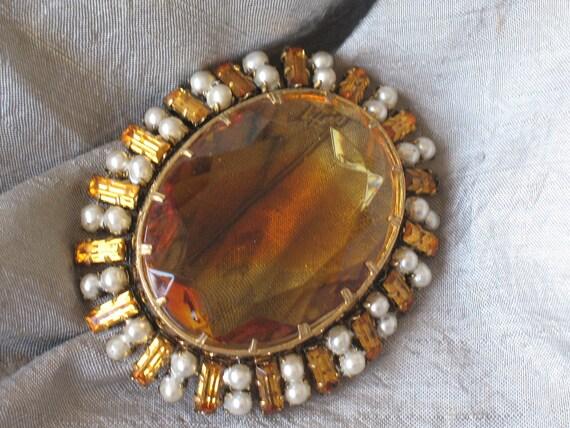 big oval shaped orange rhinestone brooch framed in a beautiful with pearls and rhinestones inlayed frame