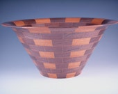 Segmented, bordered wood bowl.
