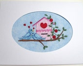Embroidered Bluebirds Sitting on Branch with Flowers next to Bird House on Blue Background in White Oval Die Cut Card Stock, blank inside