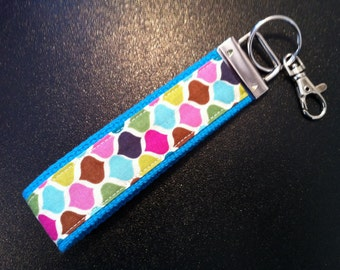Multi colored geometric print key fob wristlet on blue cotton webbing with swivel lobster clasp