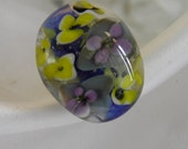 Lampwork purple and yellow floral glass ring on blue base.