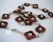 Brown flower shapes with white centers divided by white  and sterling silver round spacers