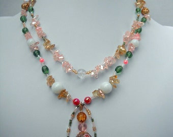 A double strand green, pink, yellow and white glass necklace with framed dangle