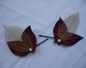 Two handmade leaf hair slides with a red and gold theme and pearl bead