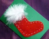 Christmas Stocking Card. Sparkly Red felt stocking hand sewn on a green background with white fluffy top. A6.