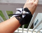 Black lace cuff with white pearl button
