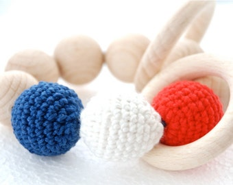 Teething toy with crochet wooden beads. Red, white, blue wooden beads rattle.