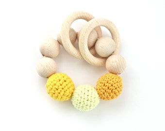 Sunny teething toy with crochet wooden beads and 2 wooden rings. Pale yellow, school bus yellow, yellow, blue wooden beads rattle.