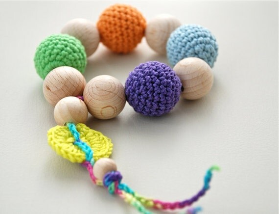 Teething toy with crochet wooden beads. Bright yellow, light blue, orange, green, violet.
