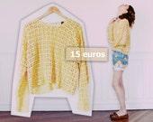 Pull en crochet jaune pastel.