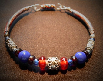 BRACELET12 is simple and sweet. It has reds, blues, and silver accents