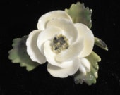 This is a lovely floral brooch.  It is a vintage white rose pin with shaded green leaves.