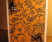 Halloween card.  Orange background with black pattterns and black cats