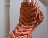 Hand knit cabled fingerless mittens in a peach orange cashmere merino wool blend