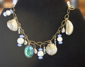 Charm bracelet of vintage detailed, jingling, silver plated shells, with vintage beads from the French General store in grays and blues.