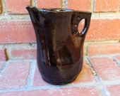 Black small altered pitcher with decorative handle