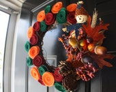 Gorgeous 10'' fall wreath adorned with eco felt rosettes, leaves, acorns, and an adorable little scarecrow
