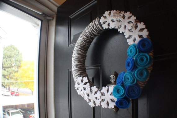 Christmas/holiday wreath, yarn-wrapped in cream and heather grey, with snowflakes and bright blue rosettes