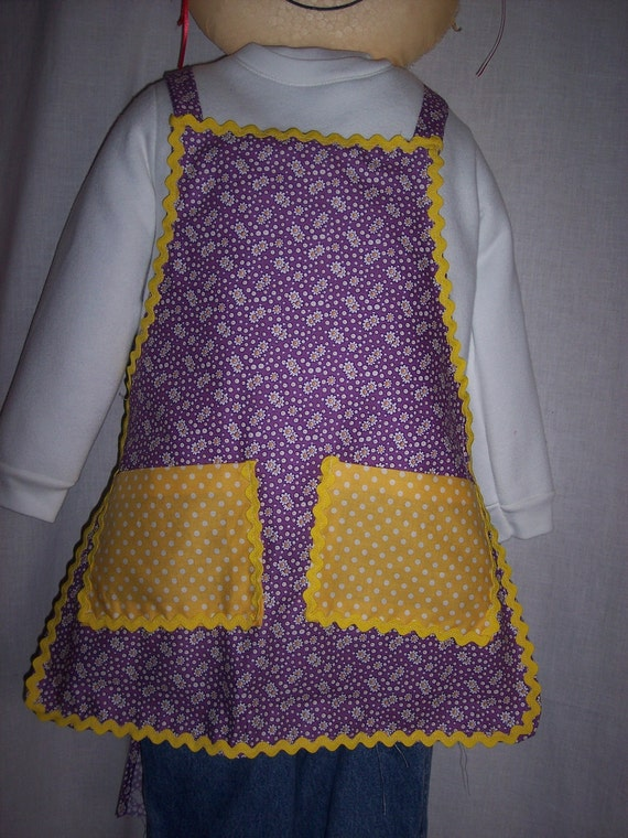Apron girls purple background with tiny white daisies and bright yellow white dotted pockets. Bright yellow rick rack trim Size 3 - 5